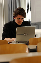 PARIS -  FRANCE - APRIL-21-2004 - Young man wearing glasses alone using a wireless - wifi - laptop computer. (PHOTO © JOCK FISTICK)..technology - business - laptop - notebook - computer - wifi - wireless - internet - communication - email - www - world wide web - web surfing - connect - connecting - connected - connectivity - study - studying - research - academics - education - student - university - young - adult - male - man - think - thinking - concentrate - concentration - concentrating