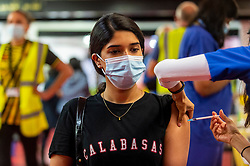 """© Licensed to London News Pictures. 27/06/2021. WATFORD, UK. Meritto Odattil (aged 21) receives a first dose of the Pfizer vaccine at a pop-up mass vaccination clinic at Watford FC's Vicarage Road Stadium as part of the """"Grab a jab"""" campaign. The NHS is also promoting a number of walk-in clinics this weekend across the capital to try to increase the number of over 18s receiving a jab as cases of the Delta variant are reported to be on the rise..  Photo credit: Stephen Chung/LNP"""
