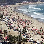 Sunbathers on Ipanema Beach, Rio de Janeiro, looking towards Arpoador point, Rio de Janeiro,  Brazil. 29th July 2010. Photo Tim Clayton..