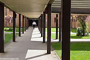A prison officer walking down a covered path inside HMP & YOI Littlehey. Littlehey is a purpose build category C prison.