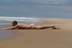 naked man stretching at the beach