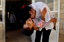 AZZARIYA, WEST BANK, MARCH 5: A nurse hugs one child at  Arba'at Batei Hahemla (Four Houses of Mercy)  for mentally disabled, autistic and physically handicapped Palestinians and others who have no family or have been abandoned March 5, 2003 in n Azzariya, West Bank. It was founded in 1940 by the late Palestinian philanthropist Catherine Siksek and is one place in the occupied territories where dozens of Palestinians and some of society's weakest members find protection and care. Outside there is war, destruction, poverty and humiliation but inside it is a place of joy that none of the devastaton has been allowed to penetrate.  The doctors and nurses work grueling days for little pay and often spend 4 hours a day just to travel a few miles to get through Israeli checkpoints but it never deters them.  (Ami Vitale/Getty Images)