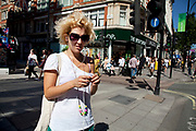 Woman wearing headphones and sunglasses at the side of a street in central London, UK. With a shock of blonde hair she has an individual style.