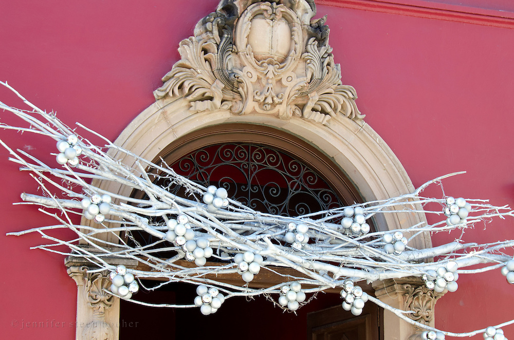 Painted silver branches with clusters of mercury glass ornaments decorate a carved stone doorway in Oaxaca, Mexico for Christmas