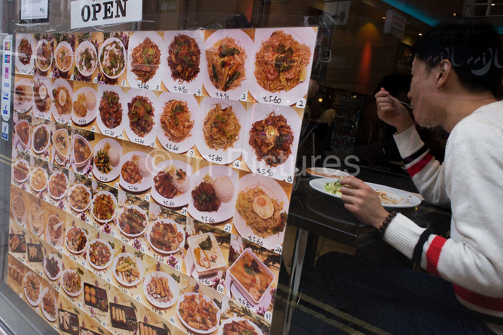 Near a menu of dishes, a customer eats a lunchtime Chinese meal in the window of a Soho eaterie. A grid of plates stuffed full of food consisting of noodles and rice items has been attached to the restaurant window to entice the customer from the street and onto a table. The man puts a fork of food into his mouth as he chats to an unseen friend at the table and a sign above says the emporium is Open.