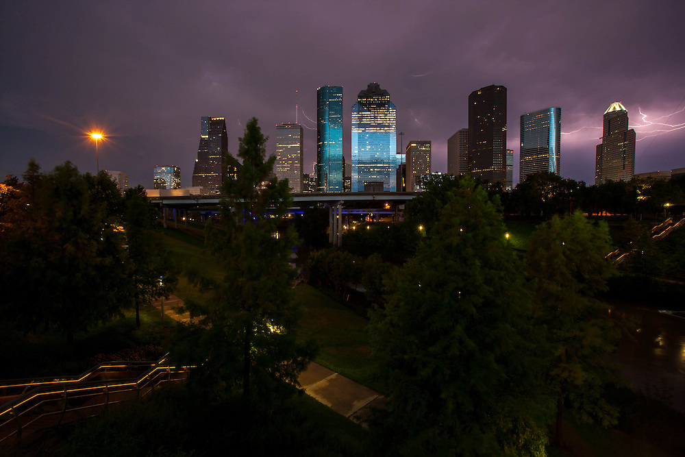 Lightning in stormy night sky over Houston, Texas skyline with Buffalo Bayou in foreground.