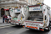 Two rubbish trucks collecting general waste drive side by side along The Strand in central London, United Kingdom.