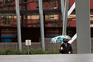 A woman with an umbrella walks across the Evan Walker Bridge during COVID-19 in Melbourne, Australia. Victoria has recorded 14 COVID related deaths including a 20 year old, marking the youngest to die from Coronavirus in Australia, and an additional 372 new cases overnight. (Photo by Dave Hewison/Speed Media)