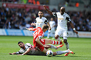 Southampton 's  Sam Gallagher is sent flying by Swansea's Jordi Amat and Dwight Tiendalli ®. Barclays Premier league match, Swansea city v Southampton at the Liberty stadium in Swansea, South Wales on Saturday 3rd May 2014.<br /> pic by Andrew Orchard, Andrew Orchard sports photography.