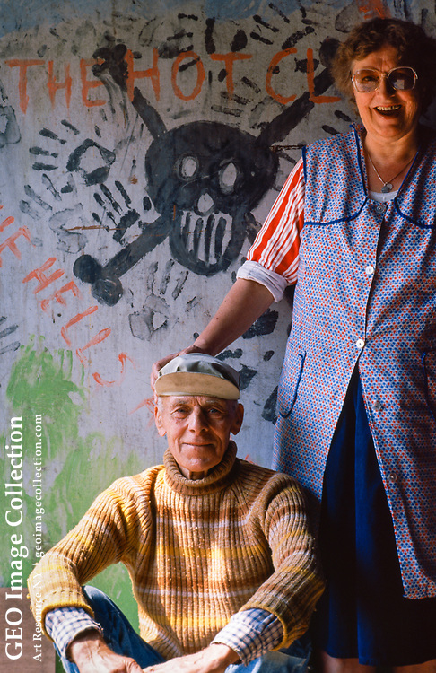 A cheerful couple of squatters living in their illegal squat loft on top floor of a warehouse. The building was abandoned. The wall is decorated with a pirate symbol.