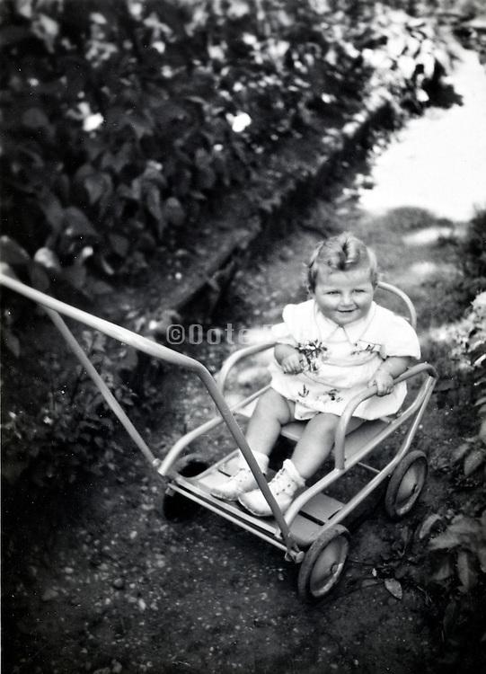 smiling toddler sitting in stroller France 1900s