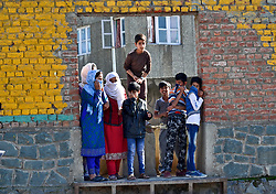 April 13, 2018 - Srinagar, J&K, India - Locals watch as protesters clash with Indian government forces in Srinagar, Indian administered Kashmir. Clashes erupted in several parts of Kashmir valley after Friday prayers over the civilian killings in army firing. Police fired tear smoke shells and pellets to disperse protesters. (Credit Image: © Saqib Majeed/SOPA Images via ZUMA Wire)