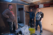 Polish builders at work in a flat in Hackney on 17th February in London, United Kingdom. Boss Blazez Luczkiewicz, Pawel Solnica and Dawid Krasuwski discuss the next days task atthe end of the day. Blazez Luczkiewicz and his Polish employees are all highly skilled builders and have lived and worked in London for years.