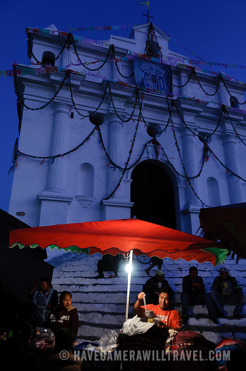 A food vendor ladles out food under an illuminated bright red umbrella in front of the steps of Santo Tomas Church on a Saturday night before the famous Sunday market day. Chichicastenango is an indigenous Maya town in the Guatemalan highlands about 90 miles northwest of Guatemala City and at an elevation of nearly 6,500 feet. It is most famous for its markets on Sundays and Thursdays.