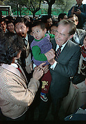 Former US President Richard M. Nixon holds a young boy as a crowd gathers during a walk around the Wangfujing Street shopping district October 30, 1989 in Beijing, China. Nixon visited as a private guest of the Chinese government.