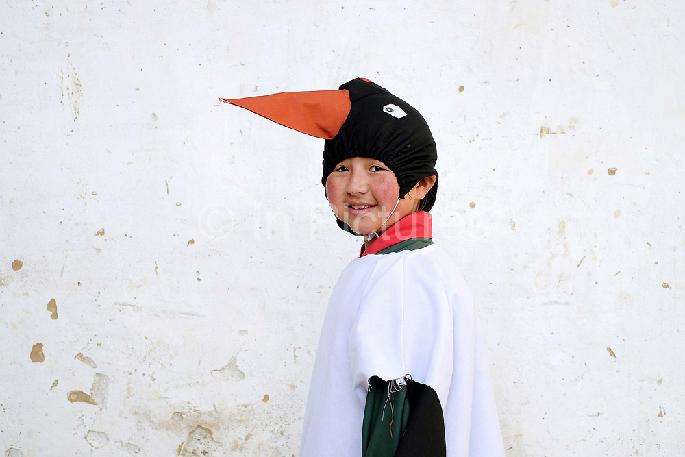 A child from Bayta Primary School dressed as a crane before performing the Black-necked Crane dance 'Ngachey Thrung Thrung Detshu' at the Black-necked Crane Festival at Gangte Goemba, Phobjikha Valley, Bhutan. Every year on November 11th, the local community hosts the festival at Gangte Goemba, to highlight the cranes significance to the valley. Phobjikha Valley is the most significant overwintering ground of the rare and endangered Black-necked Crane in Bhutan.