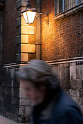 A man blurrs past the warm glow of a street lantern illuminating a wall in Bow Churchyard, in the City of London, the capital's financial district, on 26th February 2021, in London, England.