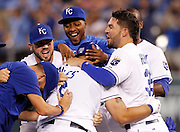 Kansas City Royals designated hitter Kendrys Morales, center, celebrates his game-winning hit with Mike Moustakas, left, Jarrod Dyson, top, Eric Hosmer, right and other players in the 10th inning of a baseball game against the Los Angeles Angels at Kauffman Stadium in Kansas City, Mo., Sunday, Aug. 16, 2015. The Royals beat the Angles 4-3. (AP Photo/Colin E. Braley)