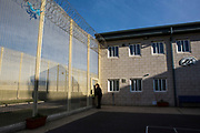 An officer leaving the excercise yard of Beaufort House, a skill development unit for enhanced prisoners. Part of HMP/YOI Portland, a resettlement prison with a capacity for 530 prisoners.Dorset, United Kingdom.