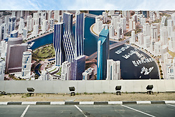 Walls around a Dubai construction site show artist renderings of the new development