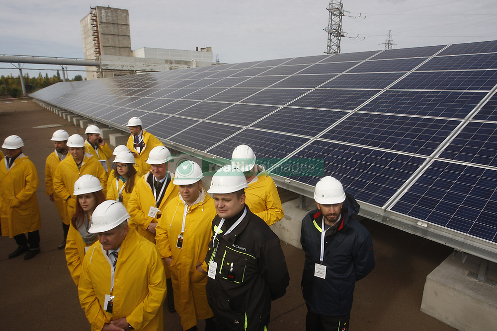 October 5, 2018 - Chernobyl, Ukraine - Visitors walk by the photovoltaic panels during an official opening ceremony of the new one-megawatt solar power plant ''Solar Chernobyl'' next to the New Safe Confinement over the 4th block of the Chernobyl nuclear plant in Ukraine, on 05 October, 2018. Ukraine on Friday launched its first solar plant in the abandoned area around its former Chernobyl power station, the scene of the worst nuclear disaster in the world. The new plant has about 3,800 photovoltaic panels installed across an area of 1.6 hectares just a hundred metres from a giant metal dome sealing the remains the Chernobyl accident on 26 April 1986. (Credit Image: © Str/NurPhoto/ZUMA Press)