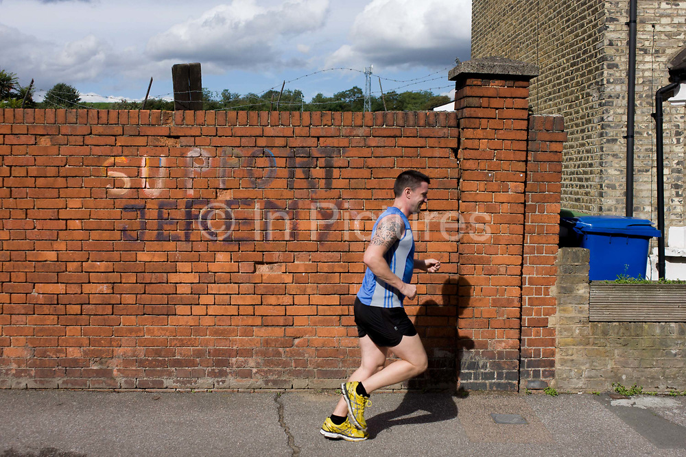 A jogger runs past some 'Support Jeremy' (Corbyn, - the left-wing Labour leader elected in September 2015) writing on a Peckham, south London brick wall. Roughly painted on to the Victorian bick wall is the message dated to the Labour leadership campaign, eventually controversially won by Corbyn. Above the writing we see barbed wire - as if the message of a dystopian, Orwellian political landscape.