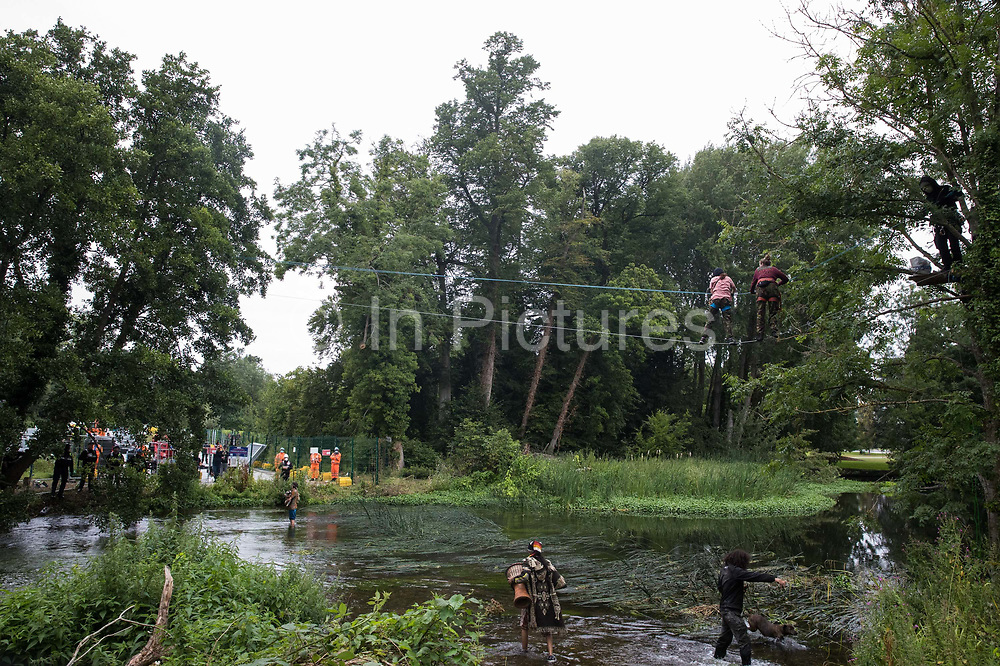 Environmental activists from HS2 Rebellion use a line above the shallow river Colne in Denham Country Park to attempt to protect an ancient alder tree from destruction in connection with works for the HS2 high-speed rail link on 24th July 2020 in Denham, United Kingdom. A large security operation involving officers from the Metropolitan Police, Thames Valley Police, City of London Police and Hampshire Police as well as the National Eviction Team ensured the removal of the tree by HS2 despite the protests by activists.