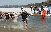 """Patrolman Ben Black wasted no time getting out Lake Winnipesaukee after bringing his """"fugitive"""" Chief Christopher Adams into the water for the annual """"Winni Dip"""" for Special Olympics on Sunday afternoon at the Margate Resort.  (Karen Bobotas/for the Laconia Daily Sun)"""