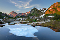 Partially thawed tarn, Yellow Aster Butte Basin. American Border Peak and Yellow Aster Butte are in the distance. Mount Baker Wilderness, North Cascades Washington