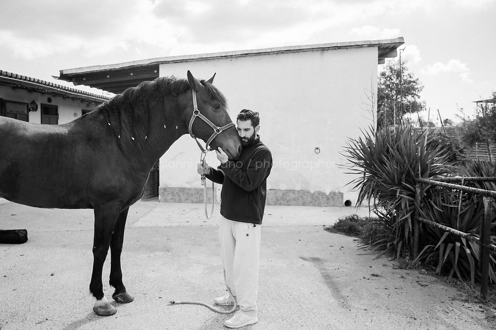 """CASTELVETRANO, ITALY - 17 FEBRUARY 2020: Giuseppe Cimarosa (36) cuddles his horse at his horse riding center. in Castelvetrano, Italy, on February 17th 2020.<br /> <br /> Giuseppe Cimarosa (36) was born into a Mafia family. He is a relative of Matteo Messina Denaro, Italy's most wanted Cosa Nostra godfather, on the run since 1993. Furthermore, investigators have long believed that Giuseppe's father, Lorenzo, occasionally provided """"support"""" for the fugitive godfather. """"My mother is a first cousin of Matteo Messina Denaro and my father was arrested as part of the Eden investigation [involving Messina Denaro]. I live in Castelvetrano [Messina Denaro's home town in Sicily, near Trapani] and I'm having a hard time . . ."""", Mr Cimarosa said.<br /> <br /> When the police came to arrest his father in 2013, Giuseppe was furious. There and then he wanted to again leave Sicily and return to Rome where he had lived and worked with horses for eight years in his 20s. He was disgusted that his father had again fallen into the clutches of their powerful relative. It was only when he went to visit his father in prison, immediately after his arrest, that Giuseppe changed his mind. In tears, his father told him that he was going to collaborate with the investigators, which he subsequently did. Realising how much his father was now risking, he opted not just to stay in Castelvetrano but also, in a certain sense, to fight back against the Mafia. What is more, he does so, not with a false identity as part of a witness protection programme, but rather by staying in his home town. His father, Lorenzo Cimarosa, died of cancer in 2017.<br /> <br /> Described as """"the last Mohican of the old mafia"""", Matteo Messina Denaro (57) is one of the world's most wanted fugitives, who has been in hiding since 1993. He was once considered a candidate to be the Sicilian mafia's boss of bosses after the deaths of Bernardo Provenzano in 2016 and Salvatore Riina in 2017. He was born into the Denaro Family (a w"""