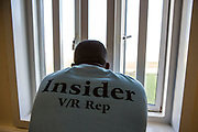 A prisoner wearing an insider jumper looks out of his cell window. HMP/YOI Portland, Dorset, United Kingdom.