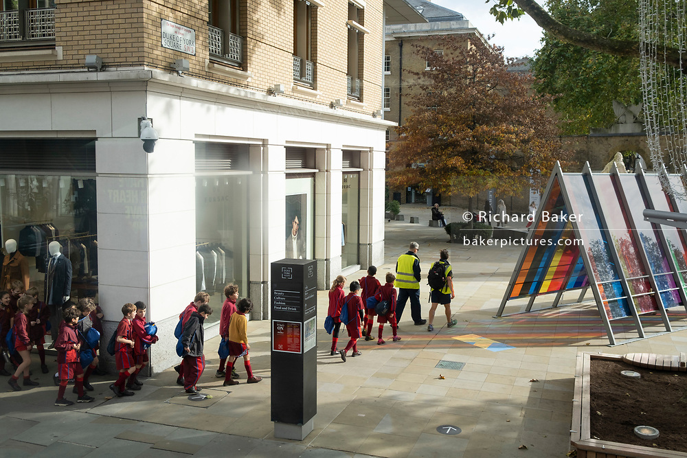 Lead by their teachers, an orderly line of local schoolchildren make their way through Duke of York Square in Chelsea, during the second wave of the Coronavirus pandemic, on 20th October 2020, in London, England.