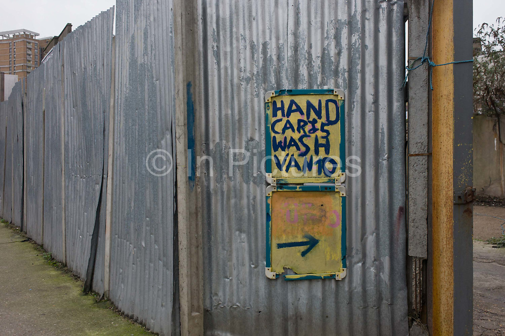 A Hand car Wash business in a London backstreet. This urban landscape is on a dull day in flat light, matching ther grey nature of this area of north London where many businesses scratch a living in industrial side streets. A hand-painted name of this business is seen on the gate door with corrugated iron sheeting forming the business's outer wall to the street.