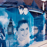 Seductive world destinations on view in a Manama City travel agency window, in the Bahrain capital. Showing the capitals of the world with the faces of European flight attendant and the children from an Asian country, the poster promises a seductive opportunity to book a trip to new experiences - the clock tower of Big Ben in London and the Sphinx of Giza in Egypt being two ideas that wealthy Bahrainis might wish to see for themselves, seen here months before the terrorist attacks on America that changed the public's attitude to flying on commercial airliners.