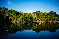 Trees and blue sky reflected on Hoan Kiem Lake in downtown Hanoi, Vietnam.