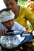 Young boy and his mother in traditional dress, about to embark on motorbike. Bali, Indonesia