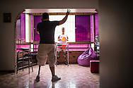 Zarevitz Camacho (c), una joven amputada bilateral juega con una pelota con Frank Avila (i), quien es unilateral y terapeuta ocupacional durante una sesión realizada en Caracas. 08 de mayo de 2014. (Foto/Ivan Gonzalez)