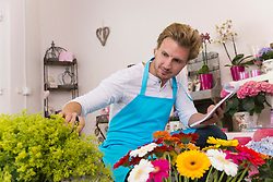 Mid adult man checking flowers in shop