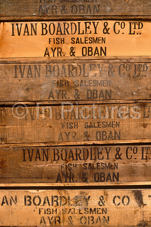 Boxes of fish products are stacked on top of each other on the quayside of the small Scottish village of Tarbert, Argyll. They are the property of fisheries company Ivan Boardley and Co. Ltd, a long-established firm in the Scotland. The boxes are of the traditional wood design with the company logo stencilled on the side telling us they are fish salesmen from Ayr & Oban, both towns on the Eastern coast of Scotland. The Five boxes are awaiting transport by road to fish processors and markets that help local fishing communities with jobs and sustainable income from this important industry when fisheries under the laws of the EU dictate what quotas boats and masters are allowed to land.