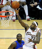 LeBron James scores on an alley-oop pass in front of Detroit's Jason Maxiell in the first half against Detroit.