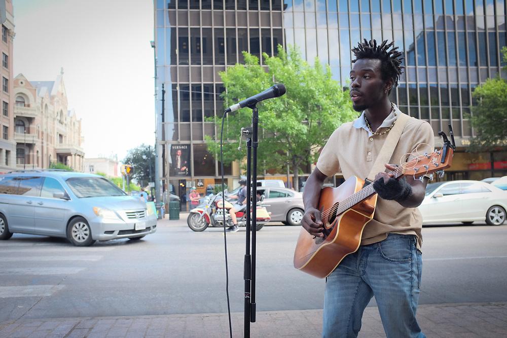 Street musician Eric Burton, using a battery powered amplifier, entertains passersby on Austin's Congress Avenue