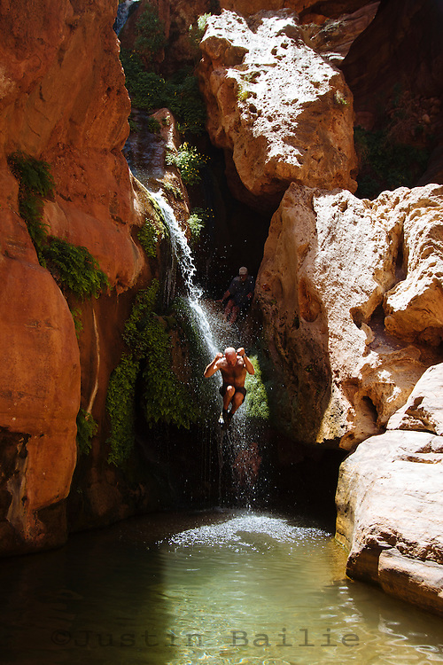 Man jumping off waterfall at Elves Chasm while on a raft trip down the  Grand Canyon National Park, AZ.
