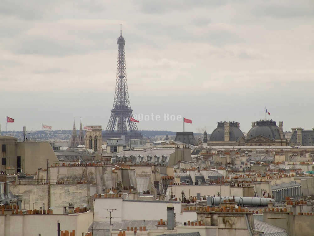 Eiffel tower and roof of Louvre seen over the roofs of Paris houses