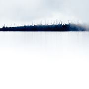 An island of trees comes out of the mist at sunrise along Yellowstone Lake.