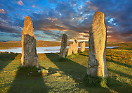 Outer row of stones, 27 metres long at sunset,  leading to the central stone circle, circa 2900BC. Calanais Neolithic Standing Stone (Tursachan Chalanais) , Isle of Lewis, Outer Hebrides, Scotland. .<br /> <br /> Visit our SCOTLAND HISTORIC PLACXES PHOTO COLLECTIONS for more photos to download or buy as wall art prints https://funkystock.photoshelter.com/gallery-collection/Images-of-Scotland-Scotish-Historic-Places-Pictures-Photos/C0000eJg00xiv_iQ<br /> '<br /> Visit our PREHISTORIC PLACES PHOTO COLLECTIONS for more  photos to download or buy as prints https://funkystock.photoshelter.com/gallery-collection/Prehistoric-Neolithic-Sites-Art-Artefacts-Pictures-Photos/C0000tfxw63zrUT4