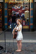 A female busker sings and plays guitar to a crowd in Covent Garden Market, London, UK
