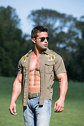 muscular man with an open army style shirt outdoors
