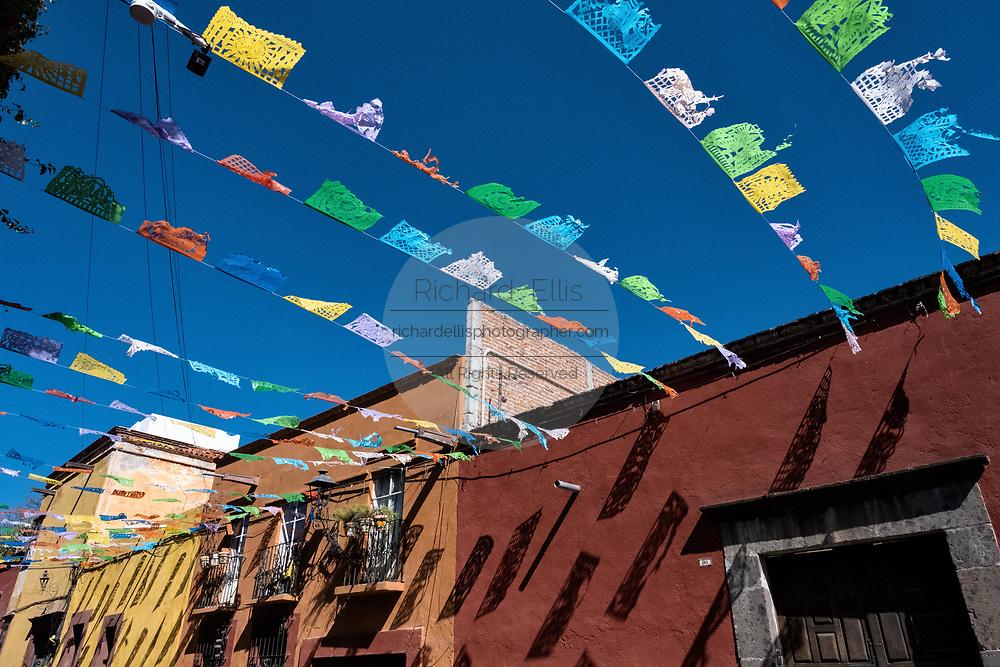 Paper fiesta banners against a clear blue sky decorate Quebrada Street in the historic center of San Miguel de Allende, Guanajuato, Mexico.