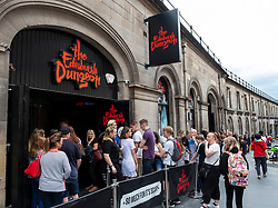 Tourists queue to enter Edinburgh Dungeon tourist attraction in Edinburgh Old Town, Scotland, UK