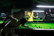 "Young workers off their shifts at one of the many shoe factories in a area known as ""Xie Du"", or shoe capital, play pool to pass the time in the city of Wenzhou, Zhejiang Province, China on 23 October, 2011. Wenzhou has seen a spate of business owners disappearing under the pressure of debt, as small and medium size businesses face increasing difficulties in securing loans, while the slow recovery of the European and U.S. economies continues to disappoint exporters."